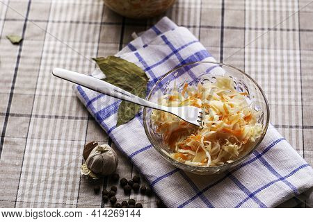 Sauerkraut In A Glass Plate On A Napkin On The Table A Metal Fork Is Stuck In The Cabbage Next To Ga