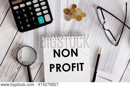 Non Profit Written In A White Notepad Near A Calculator, Cash, Glasses, A Magnifying Glass And A Pen