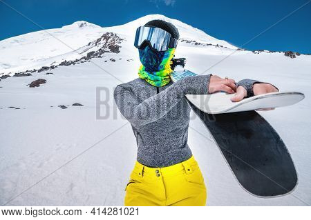 A Young Slender Woman In A Ski Mask Hat And A Comforter On Her Face Stands Without A Jacket In The S