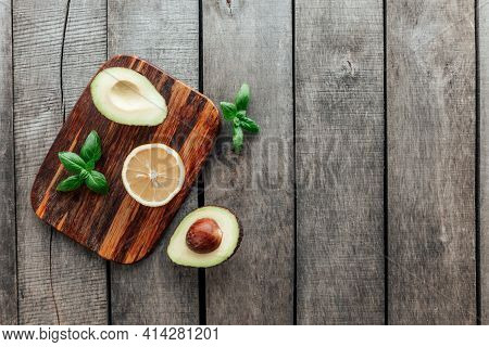 Healthy Eating Concept Flat Lay. Mediterranean Diet, Cutting Board With Avocado Halves, Kernel, Basi