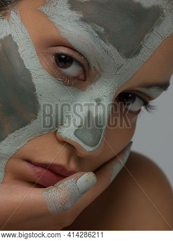 Skin Care Mask. Closeup Portrait Of Attractive Young Woman With Grey Clay Facial Mask On Healthy Fre