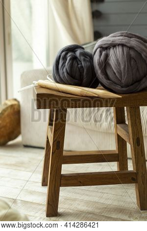 Two Large Balls Of Merino Wool Lying On A Wooden Stool With Wooden Knitting Needles Against The Back