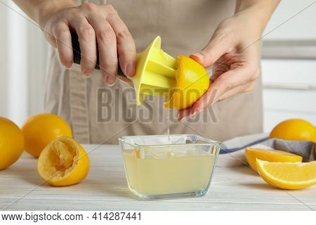 Woman Squeezing Lemon Juice With Reamer At Table, Closeup
