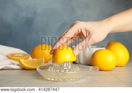 Woman Squeezing Lemon Juice At Wooden Table, Closeup