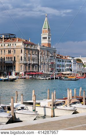 Taxi Boats On Calm Water Of Grand Canal Im Venice. Old Houses And Tower Of St Marks Campanile By Can