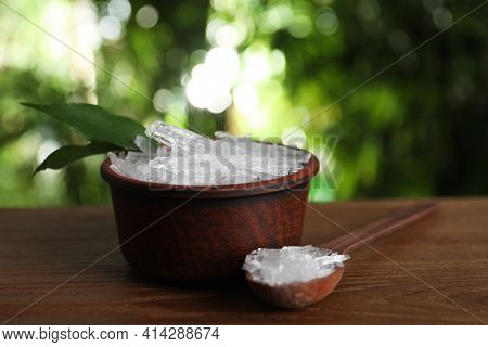 Bowl And Spoon With Menthol Crystals On Wooden Table Against Blurred Background