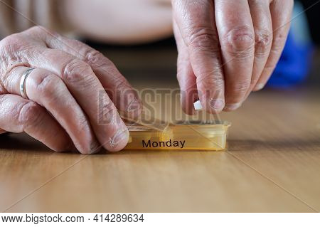 Closeup Of An Elderly Senior Woman's Hands Taking Her Medication For The Week In A Pill Box On Woode