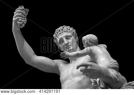Statue of Dionysus or Bacchus with bunch of grapes isolated on black.