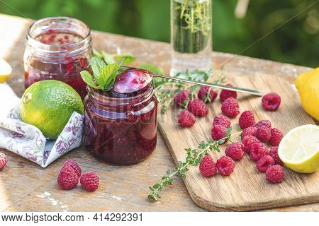 Raspberry Jam And Fresh Raspberry On A Rustic Wooden Table In The Garden. Summer Sunny Day, Close Up