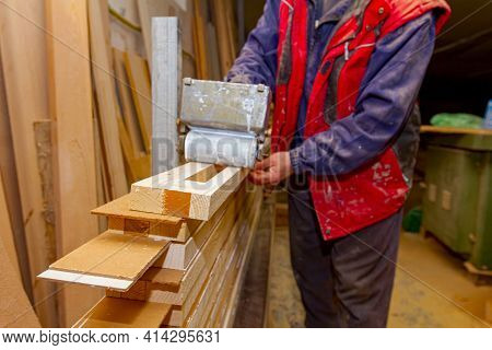 Carpentry Worker Uses Handy Roller Tool, Spreader For Applying Adhesive On The Wooden Surface Profil