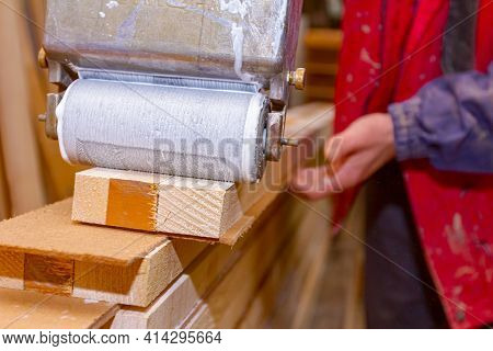 Close-up Shot On Carpentry Worker That Uses Handy Roller Tool, Spreader For Applying Adhesive On The