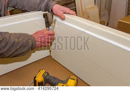 Carpentry Worker Is Cutting Rubber Tape To Facilitate Putting Together Wooden Pieces Of Door Frame I