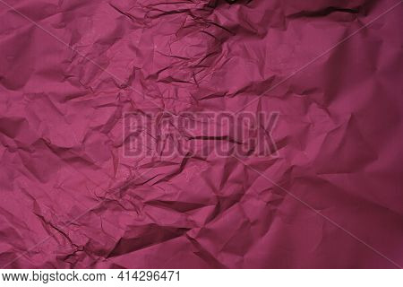 Dark Red Background From Wrapping Crumpled Paper. Burgundy Sheet Of Crumpled Paper Top View. The Cre