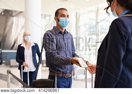 Indian passenger wearing protective face mask showing e-ticket to flight attendant at boarding gate. Mixed race businessman showing boarding pass on mobile phone to air hostess during covid pandemic.
