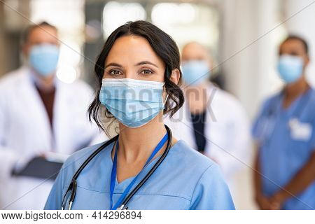 Close up face of confident female nurse in front of his medical staff looking at camera while wearing protective face mask due to covid-19 virus. Smiling surgeon standing  with team in background.