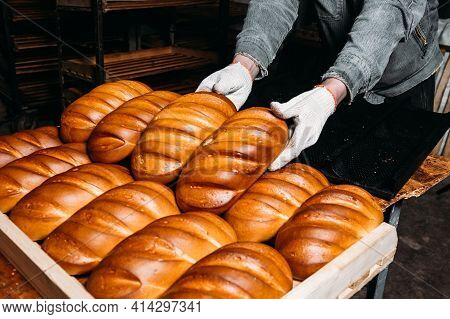 A Man Puts Freshly Baked Bread On A Tray. Baker Puts A Tray With Fresh Pastries On The Shelf Against