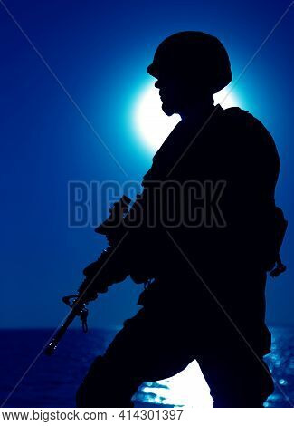 Silhouette Of Army Infantry Shooter Patrolling Seacoast With Service Rifle At Night. Army Special Fo