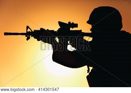 Silhouette Of Modern Army Infantry Soldier Standing On Background Of Setting Sun And Aiming Assault