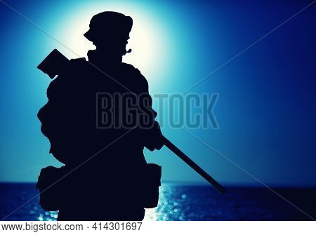 Silhouette Of Army Elite Forces Fighter Standing With Sniper Rifle On Background Of Blue Sky With Mo