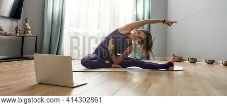 Athletic Girl Stretching While Sitting On A Sports Mat At Home. Skinny Girl Doing Physical Exercisin