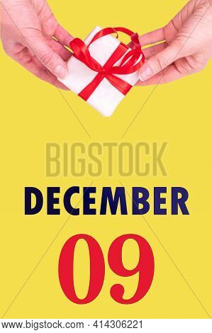 December 9th. Festive Vertical Calendar With Hands Holding White Gift Box With Red Ribbon And Calend