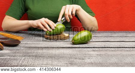 Girl Cuts Avocado On A Round Board. The Girl Cuts A Ripe Green Avocado With A Knife. The Fruits Are