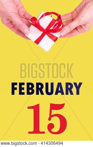 February 15th. Festive Vertical Calendar With Hands Holding White Gift Box With Red Ribbon And Calen