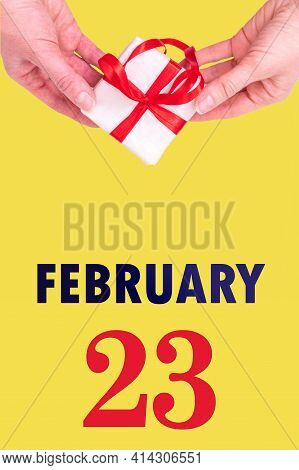 February 23rd. Festive Vertical Calendar With Hands Holding White Gift Box With Red Ribbon And Calen