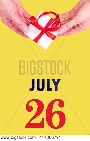 July 26th. Festive Vertical Calendar With Hands Holding White Gift Box With Red Ribbon And Calendar