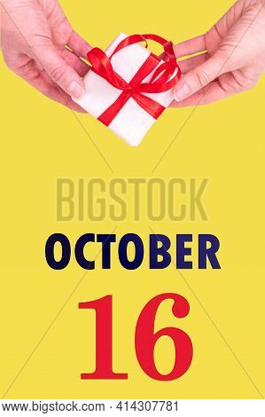 October 16th. Festive Vertical Calendar With Hands Holding White Gift Box With Red Ribbon And Calend