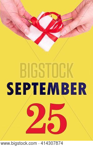 September 25th. Festive Vertical Calendar With Hands Holding White Gift Box With Red Ribbon And Cale