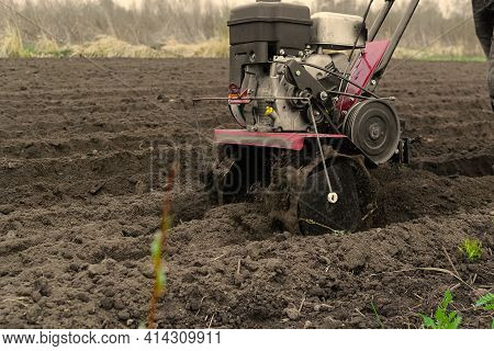 Motor Cultivator For Digging Up The Earth. Spring Planting And Digging In The Damp Earth.garden And