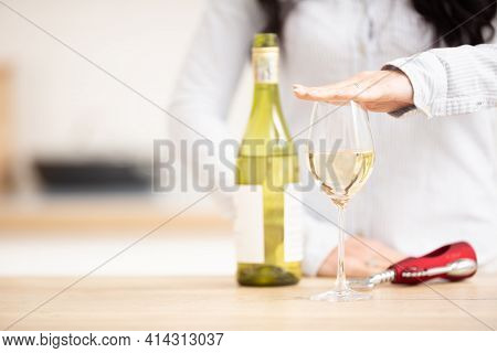 Woman Holding Hand Above The Glass Of White Wine To Express She Had Enough.