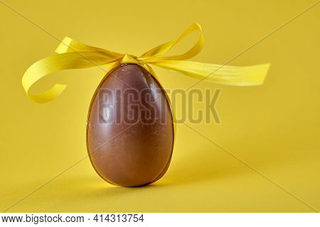 A Milk Chocolate Egg In A Yellow Ribbon With A Bow On A Gentle Yellow Background. Easter Concept.