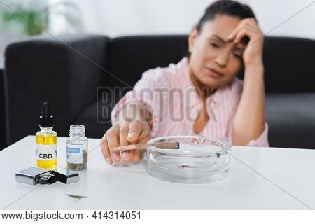 Blurred African American Woman Suffering From Migraine And Reaching Joint In Astray Near Bottles Wit
