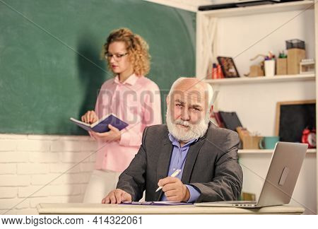Check It Out. Course In School. Student And Tutor With Laptop. Answering Student Girl With Tutor Man