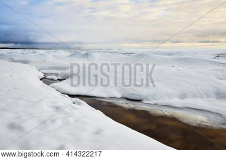 Beautiful Northern Snowy Landscape With Horizon And Cloudy Sky And With Water Through The Foreground