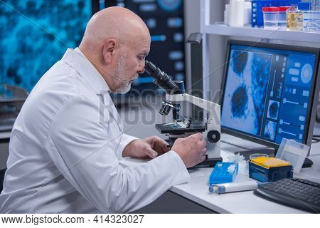 Elderly professor is doing a science experiment in a modern laboratory. Genetic engineers workplace. The concept of science, medicine and vaccine development.