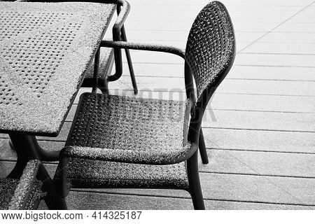 Abstract Snow-covered Parts Of The Chair And Table Of Black Color And Closeup Outdoors With White Sn