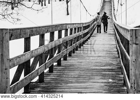 In The Black-and-white Photo Are Represented Two Teenagers Walk Together Next To An Old Pedestrian S