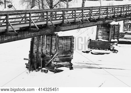 Abstract Empty Old Wooden Bridge Close-up On The River And With Snow In Winter Or Spring On A Black