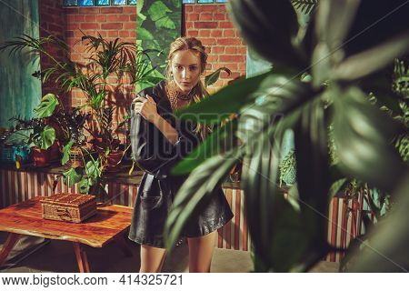 Stylish young woman model poses in apartments in black leather coat and gold and pearl jewelry. Fashion and jewelry.