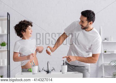 Smiling Arabian Man Holding Deodorant Near Son And Sink In Bathroom.