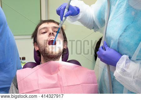 Team Of Dental Surgeons Performs Surgery On Teeth. In A Modern Clinic. Young Dentist. Teamwork. Toot