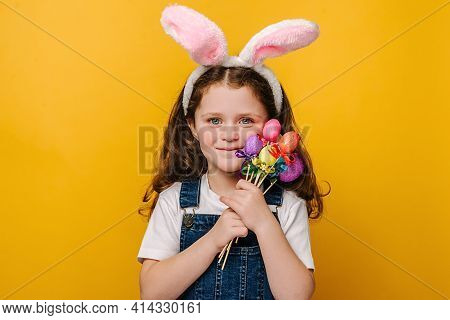 Good Looking Smiling Preschool Girl Kid With Bunny Fluffy Ears, Holds Painted Eggs On Sticks, Has A