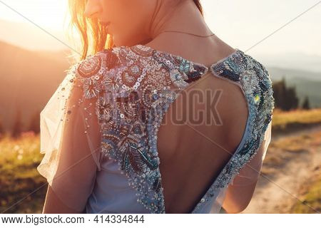 Beautiful Bride In Blue Wedding Dress With Embroidery Decoration And Bare Back Walking In Mountains