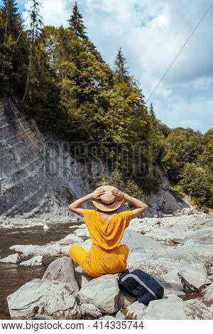 Portrait Of Young Woman Tourist Relaxing By Mountain River Enjoying Landscape Alone. Traveler Sittin