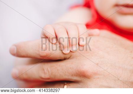 Closeup Of Baby Fingers Holding Father Parent Hand Palm. Baby Trust And Confidence In Adult Parent.