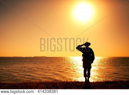 Silhouette Of Saluting Commando Soldier, Army Infantryman Standing On Shore During Sunset Or Sunrise