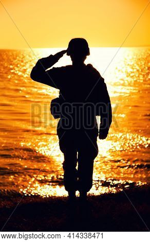Silhouette Of Army Soldier, Marines Fighter In Helmet And Ammunition Saluting While Standing On Seas